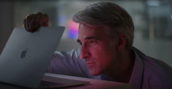 Craig Federighi looking wistfully at a Mac laptop in a darkened room